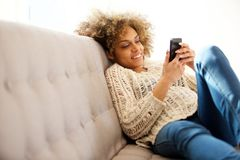 Modische junge Frau, die zu Hause sitzt und Mobiltelefon betrachtet lizenzfreie stockfotos