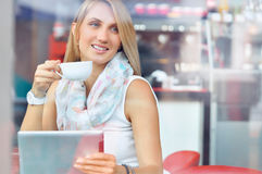 Modische junge Frau im Café mit Tasse Kaffee und Tablette des Bildschirm- Lizenzfreies Stockfoto