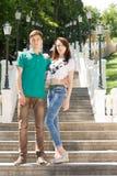 Modische junge Paare, die auf einem Flug der Treppe aufwerfen Lizenzfreie Stockfotos