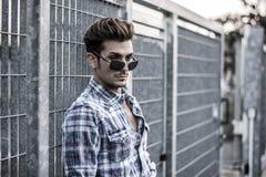Modische kühle stehende Außenseite des jungen Mannes, lehnend lizenzfreies stockfoto
