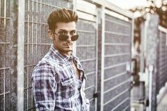 Modische kühle stehende Außenseite des jungen Mannes, lehnend am Metalltor Lizenzfreies Stockbild