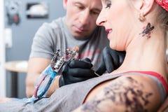 Modische lächelnde Frau beim Erhalten einer schmerzlosen neuen Tätowierung Stockbild