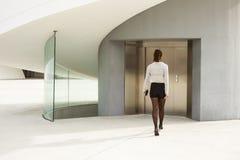 Modische moderne Geschäftsfrau, die Unternehmensgebäude betritt Stockbilder