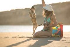 Modische moderne Hippie-Frau des attraktiven Sitzes, die mit Strohhündchen auf Strand spielt Lizenzfreies Stockfoto