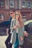 Modische moderne Paare, die nahe dem Auto stehen Stockfotografie