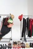 Modische Schuhe und Hüte mit Zubehör auf Kleidungs-Schiene Lizenzfreie Stockbilder