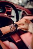 Modische schwarze Uhr auf Frauenhand Lizenzfreie Stockfotos