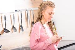 Modische stilvolle junge Frau, die ihr Mobile verwendet Lizenzfreies Stockfoto