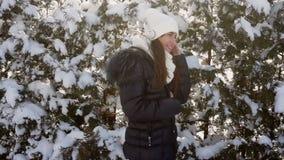 Modische Winterfrau in den Kopfhörern hörend Musik im Park stock video footage