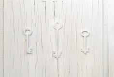 Modischer Dekor mit drei Schlüsseln auf einer alten grauen gebrochenen Tür, Weinlesezusammenfassungsdesign Stockfoto
