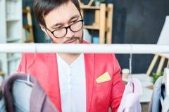 Modischer Designer, der Kleidung auf Aufhängern überprüft Stockfotos