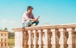 Modischer erwachsener Mann mit Smartphone oder digitaler Tablette Stockfotografie