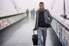 Modischer gutaussehender Mann, der mit einem Koffer geht Stockbild