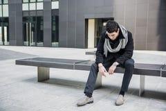Modischer hübscher junger Mann, der auf Steinbank sitzt Stockfotos