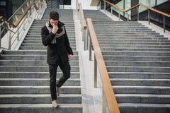 Modischer hübscher junger Mann auf die Wintermode, die auf einem langen Treppenhaus steht Stockfotografie