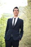 Modischer junger Geschäftsmann, der draußen lächelt Stockfotos