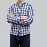 Modischer junger Mann, der das blaue karierte Hemd, stehend gegen einen grauen Hintergrund trägt stockfoto