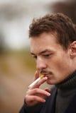 Modischer junger Mann, der eine ungesunde Zigarette raucht Stockbild