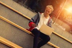 Modischer Kerl, der mit einem Laptop und einer Kreditkarte sitzt Stockfotos