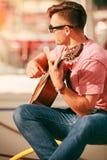 Modischer Kerl mit der Gitarre im Freien Lizenzfreie Stockfotos