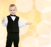 Modischer kleiner Junge in einem schwarzen Anzug mit einer Bindung Lizenzfreie Stockbilder
