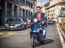 Modischer Mann auf Roller in der Stadt Stockbild