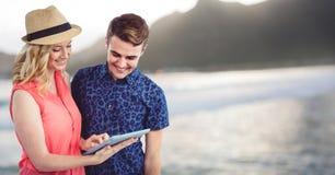 Modischer Mann und Frau mit Tablette gegen undeutliche Küstenlinie Lizenzfreies Stockbild