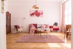 Modischer Wohnzimmerinnenraum mit grauer Couch mit rosa Pastellkissen und Decke, stilvoller beige Lehnsessel mit Burgunder-Kissen lizenzfreie stockbilder