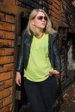 Modisches blondes Mädchen, das an einer Backsteinmauer sich lehnt Stockbilder