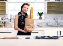 Modisches Mädchen in der Küche mit Einkaufstasche Lizenzfreies Stockfoto