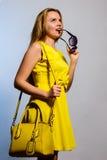 Modisches Mädchen mit gelber Handtasche und Sonnenbrille in der Hand stockbilder