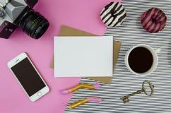 Modisches Modell mit Handy, Blatt des leeren Papiers auf Kraftpapier-Umschlag, Kappe des Kaffees, Retro- Fotokamera und Bonbons Stockbilder