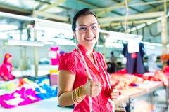 Modista asiática en una fábrica de la materia textil Foto de archivo