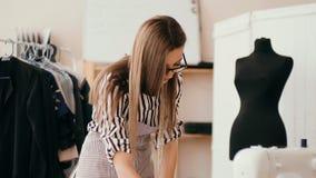 Modista de sexo femenino que trabaja en una máquina de coser en su estudio soleado Diversos artículos y telas de costura que pone almacen de metraje de vídeo