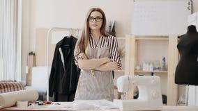 Modista de sexo femenino que trabaja en una máquina de coser en su estudio soleado Diversos artículos y telas de costura que pone almacen de video