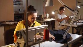 Modista que trabaja en una máquina de coser en estudio del sastre en la tabla Empleo profesional de la costurera en la moda almacen de metraje de vídeo