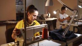 Modista que trabaja en una máquina de coser en estudio del sastre en la tabla Empleo profesional de la costurera en la moda almacen de video