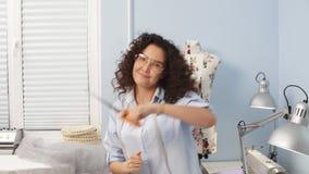 Modista sonriente que usa las tijeras para hacer corte de pelo Costurera loca del estilo almacen de video