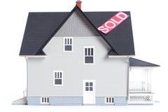 Modèle architectural à la maison avec le signe vendu, d'isolement Photographie stock