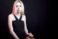 Modèle blond attrayant sur un fond noir Images stock