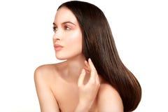 Modèle de beauté montrant la peau parfaite et les longs cheveux bruns sains Photographie stock libre de droits