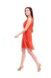 Modèle femelle assez jeune dans la robe marchant sur le fond et le sourire blancs Photographie stock