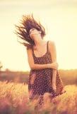 Modèle romantique dans la robe de Sun dans le domaine d'or au coucher du soleil Photo stock