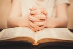 Modlić się ręki na Otwartej biblii Obrazy Stock
