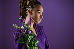 Modna amerykanin afrykańskiego pochodzenia dziewczyna pozuje z purpurowym eustoma kwitnie, obraz royalty free