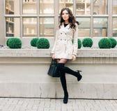 Modna brunetki dziewczyna z długie włosy ubierającym w deszczowu, wysoka czarna wysokość heeled buty z torebką pozuje blisko a Zdjęcia Stock