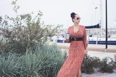 Modna brunetki kobieta jest ubranym długą czerwieni suknię w okularach przeciwsłonecznych bierze spacer blisko morza, molo z jach Zdjęcie Royalty Free