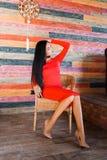 Modna brunetki kobieta z długie włosy i czerwonym smokingowym obsiadaniem na krześle w domu i patrzejący daleko od zdjęcia stock