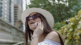 Modna dama stoi blisko kamiennych poręczy i opowiada na telefonie komórkowym zbiory