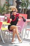 Modna dama z małym czerni smokingowym i czerwonym szalika obsiadaniem na krześle w restauraci, plenerowy strzał w słonecznym dniu fotografia royalty free